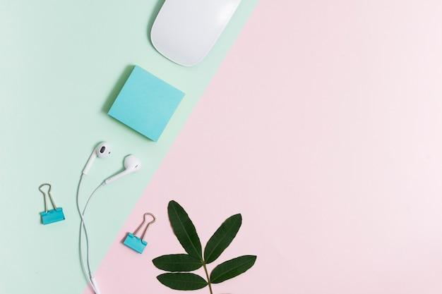 Espace de travail avec écouteurs et souris sur fond rose et vert
