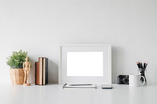 Espace de travail élégant avec affiche, livre et gadget. bureau et espace de travail