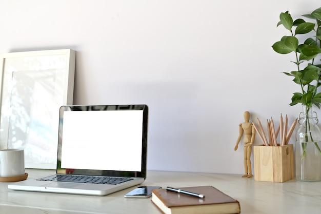 Espace de travail élégant avec ordinateur portable, fournitures créatives, plante d'intérieur et livres au bureau.