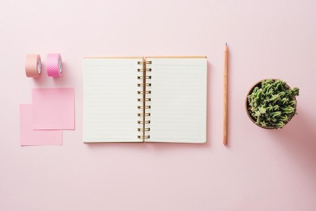 Espace de travail élégant et papeterie blanche vierge sur fond rose pastel, espace de copie. modèle pour votre conception.