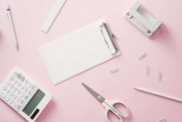 Espace de travail élégant avec papeterie blanche vierge sur fond rose pastel, espace de copie. modèle pour votre conception.