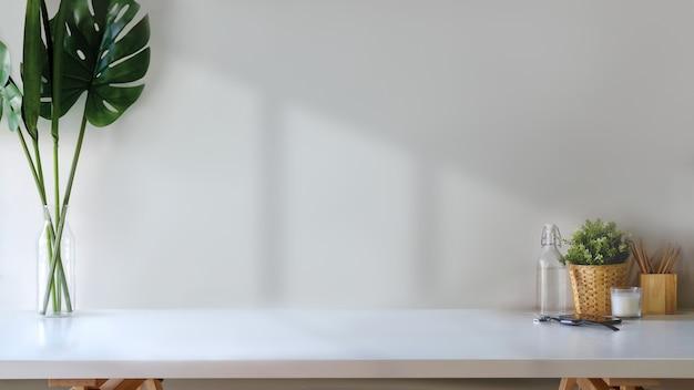Espace de travail et espace de copie, table en bois blanc avec plante, tasse à café et autres choses.