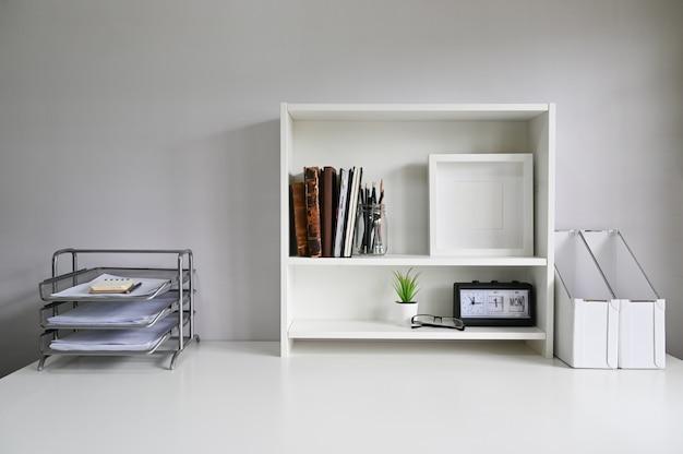 Espace de travail avec étagères et fournitures de bureau sur la table.