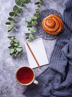 Espace de travail féminin avec chignon, tasse de thé et cahier. lay plat, vue de dessus