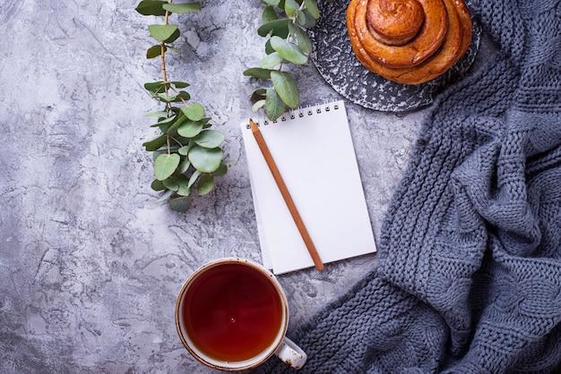 Espace de travail féminin avec chignon, tasse de thé et cahier