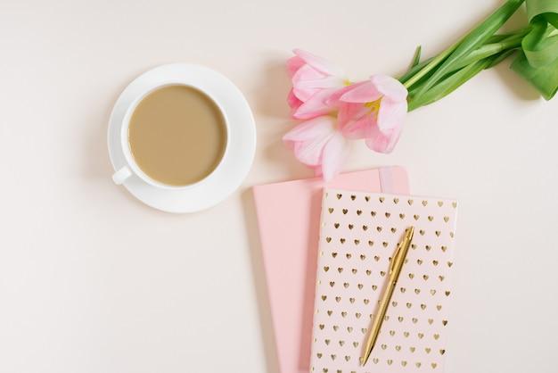 Espace de travail féminin avec des fleurs de tulipes roses, un journal intime, une tasse de thé et un beignet sur fond beige. mise à plat. arrière-plan de la vue de dessus.