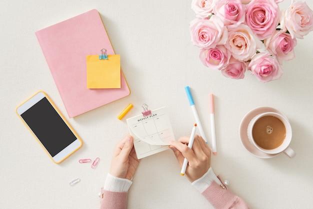 Espace de travail féminin avec ordinateur, bouquet de fleurs roses,