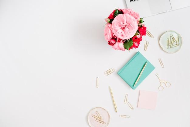 Espace de travail féminin avec ordinateur portable, bouquet de roses roses et rouges, accessoires dorés, journal à la menthe sur blanc