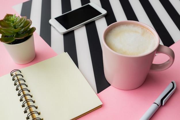 Espace de travail féminin avec smartphone, tasse de café et bloc-notes vide avec espace copie sur fond rose