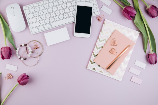 Espace de travail féminin avec tulipes, clavier, lunettes, agenda et clips dorés sur violet