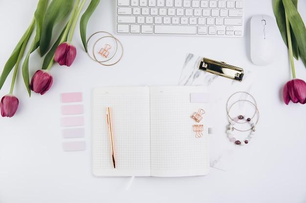 Espace de travail féminin avec tulipes, clavier d'ordinateur, pinces dorées sur fond blanc