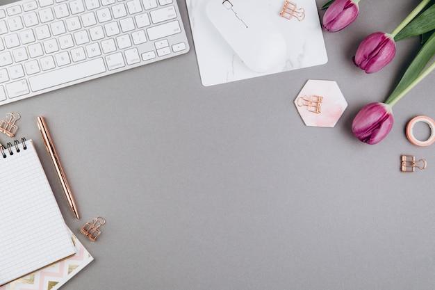 Espace de travail féminin avec tulipes, clavier, pinces dorées sur fond gris