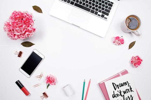 Espace de travail de femme avec carnet, fleur d'oeillet rose, sur fond blanc.
