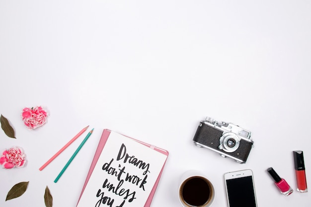 Espace de travail femme avec carnet, fleur d'oeillet rose, smartphone, rouge à lèvres