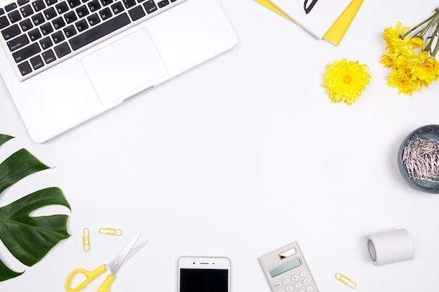 Espace de travail femme avec ordinateur portable, carnet, fleur jaune et smartphone sur fond blanc