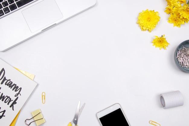 Espace de travail femme avec ordinateur portable, fleur jaune et smartphone sur fond blanc