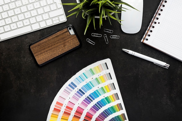 Espace de travail de graphiste avec bureau et clavier noir, plante, souris, bloc-notes, smartphone et stylo