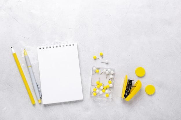 Espace de travail gris avec bloc-notes et accessoires de papeterie jaunes. illuminating yellow et ultimate grey, couleurs de l'année 2021 - image