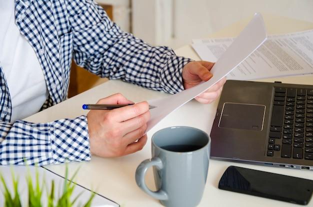 Espace de travail en gros plan : ordinateur portable, tasse à café, téléphone. les mains des femmes prennent des notes sur une feuille de papier blanche