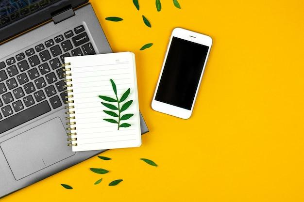 Espace de travail indépendant avec ordinateur portable, bloc-notes et smartphone, feuilles vertes printanières sur fond jaune, photo de l'espace de copie
