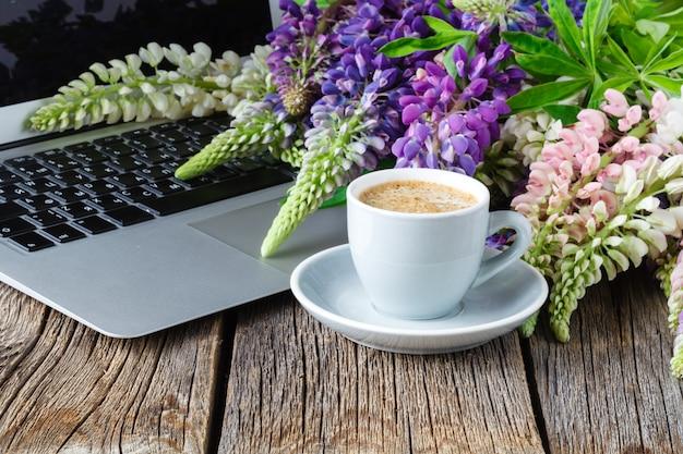 Espace de travail ou lieu de travail avec ordinateur portable, fleurs et café