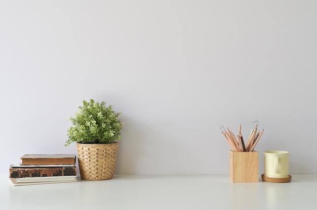 Espace de travail avec des livres, du café, un crayon et une décoration végétale sur un bureau blanc.