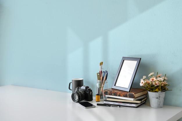 Espace de travail loft avec appareil photo argentique vintage, livres, tasse à café, cadre de poster et espace de copie.