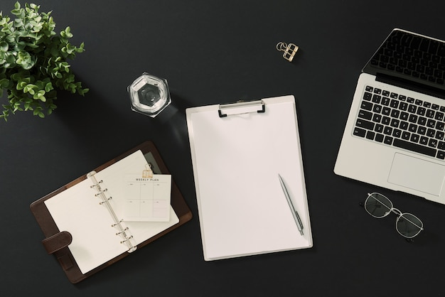 Espace de travail masculin avec cahier en papier, stylo, accessoires sur noir.