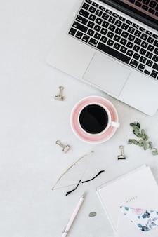 Espace de travail minimal de bureau à domicile avec ordinateur portable, café. cahier, eucalyptus sur gris