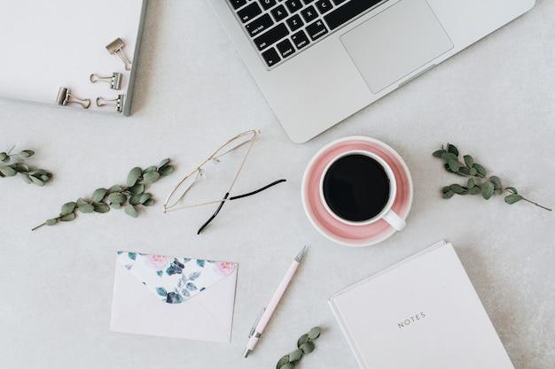 Espace de travail minimal de bureau à domicile avec ordinateur portable, café, ordinateur portable, eucalyptus, enveloppe