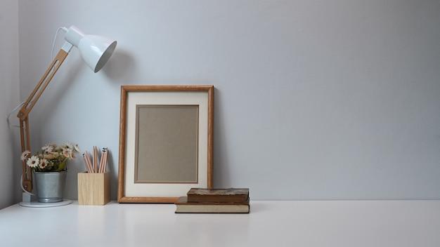 Espace de travail minimal avec cadre, crayons, tasse à café, lampe et vieux livre sur table blanche.