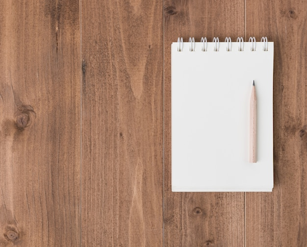 Espace de travail minimal, cahier et crayon brun sur fond de table en bois, vue de dessus