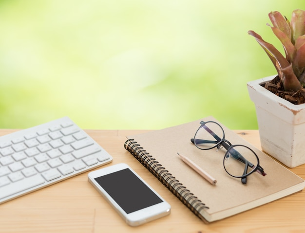 Espace de travail minimal avec clavier, smartphone, lunettes, ordinateur portable et crayon sur table en bois