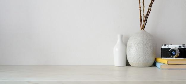 Espace de travail minimal avec espace de copie, appareil photo et fournitures de bureau sur un bureau blanc et un mur blanc