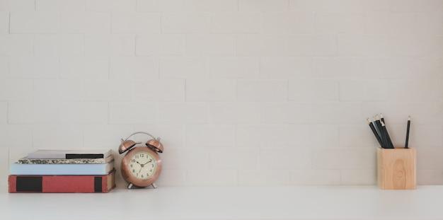 Espace de travail minimal avec espace de copie et fournitures de bureau sur un bureau en bois blanc et mur de briques blanches