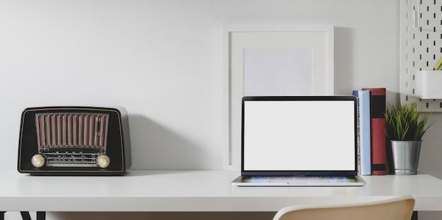 Espace de travail minimal avec un ordinateur portable à écran blanc ouvert avec des fournitures de bureau et une radio vintage