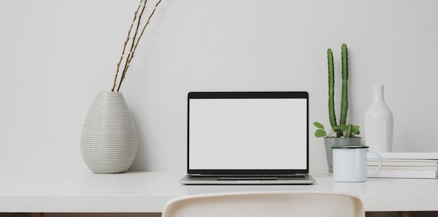 Espace de travail minimal avec un ordinateur portable ouvert et des décorations sur une table blanche et un mur blanc