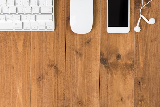 Espace de travail minimal, ordinateur, smartphone, écouteur sur table en bois