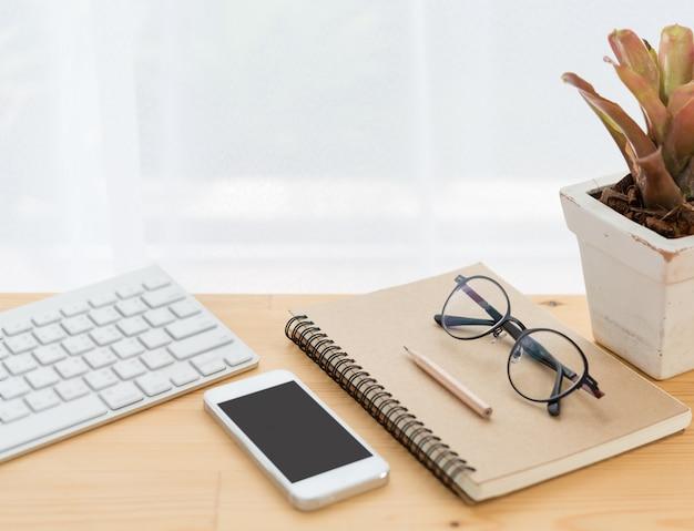 Espace de travail minimal, ordinateur, smartphone, ordinateur portable, crayon et lunettes sur table en bois