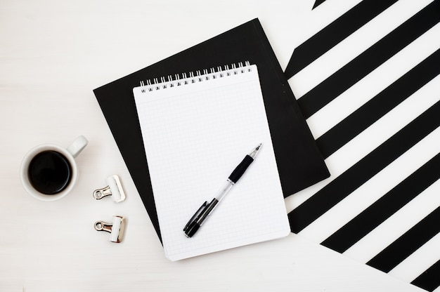 Espace de travail minimaliste élégant avec bloc-notes, crayon et tasse de café