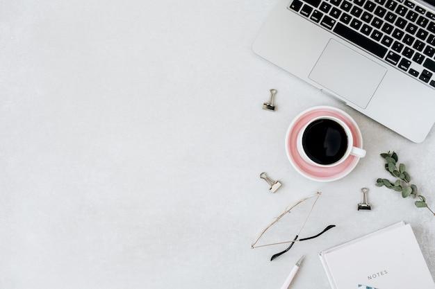 Espace de travail minimaliste pour le bureau à domicile. ordinateur portable, café, verres, cahier, eucalyptus sur blanc