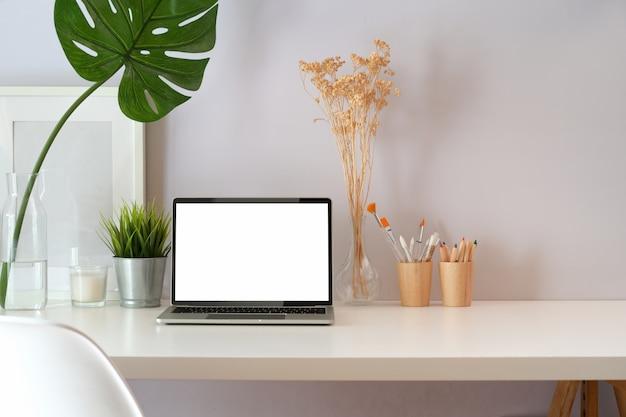 Espace de travail moderne avec ordinateur portable à écran blanc