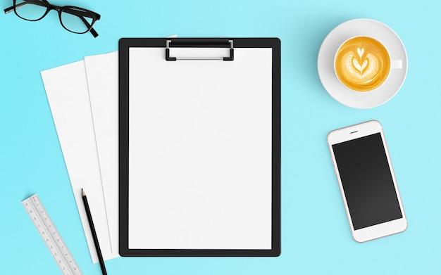 Espace de travail moderne avec une tasse de café, du papier vierge, un ordinateur portable et un smartphone de couleur bleue