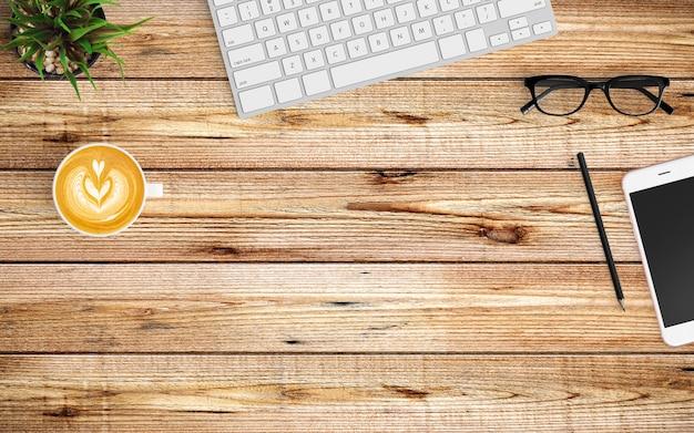 Espace de travail moderne avec tasse à café, tablette ou smartphone et clavier sur bois