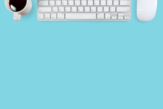 Espace de travail avec ordinateur et café sur pastel bleu