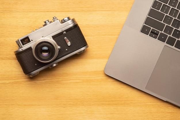 Espace de travail avec ordinateur portable et appareil photo sur table en bois. vue de dessus