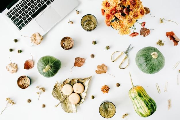 Espace de travail avec ordinateur portable, bouquet de chrysanthème, citrouille, feuilles, ciseaux sur blanc