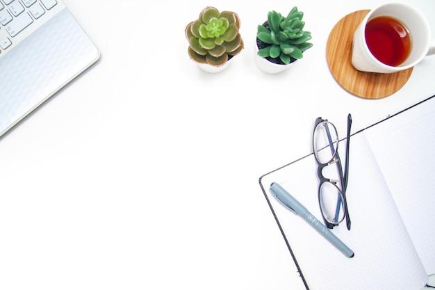 Espace de travail avec ordinateur portable, cahier, carnet de croquis, succulent, tasse de thé sur fond blanc.