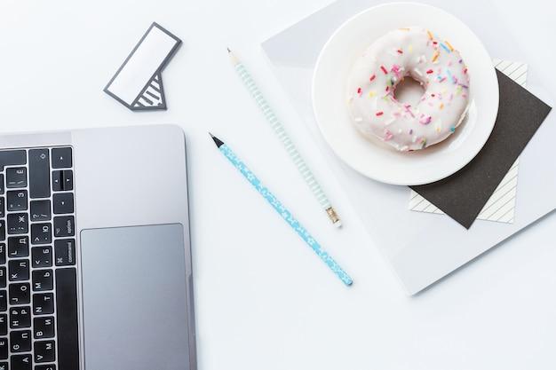 Espace de travail avec ordinateur portable, crayon, cahier et beignet sur fond blanc