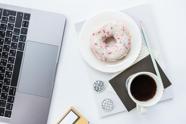 Espace de travail avec ordinateur portable, crayon, cahier, tasse à café et beignet sur fond blanc.